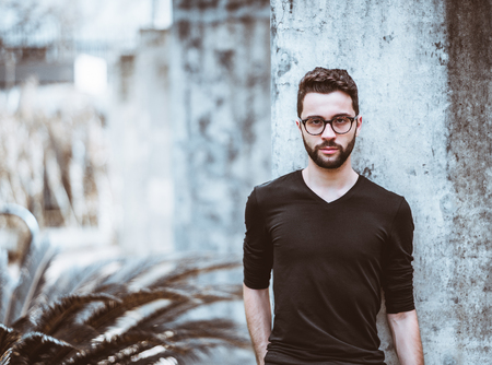 Portrait of serious handsome bearded hipster guy in the glasses and black t-shirt standing in front of the concrete wall with bush and copy space place for your logo, text message or advertising