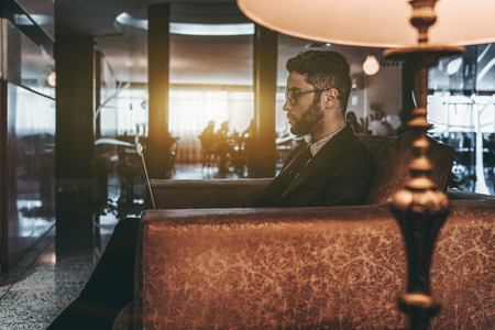 Side view of handsome bearded Caucasian businessman in glasses and formal suit sitting in front of the meeting rooms in luxury office area in classical golden style and working with his laptop