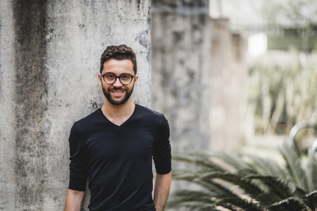 Handsome smiling bearded hipster guy in glasses and t-shirt is leaning on the concrete wall behind him; portrait of cheerful young Brazilian man outdoors with copy space place for your logo or text Standard-Bild