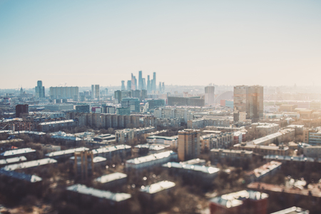 True tilt-shift view of autumn or spring cityscape with skyscrapers and residential houses, with focus on the middle zone of the image; background and foreground are blurred and have strong bokeh Banco de Imagens