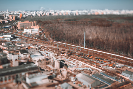 True tilt-shift view from the high point of railway track, focus on the railroad; multiple carports and industrial buildings in defocused foreground; partly snowed forest park in the blurry background