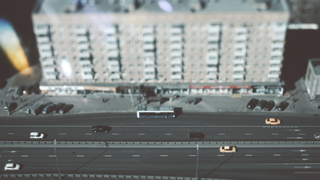 True tilt-shift shooting of highway in metropolis from the high point: residential building, the road in focus with cars, taxies and public transport, crosstown traffic, and street lanterns, sunny day