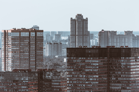 Close-up urban view of multiple office buildings and residential houses, facades with many windows and external air conditioning units, cold blue color tint, winter or autumn sunny day, dull cityscape
