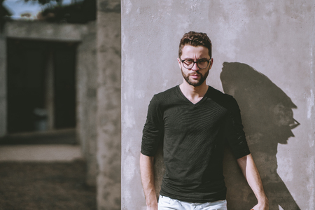 Angry handsome young bearded hipster guy in casual outfit and eyeglasses is leaning against the wall on a sunny day, with copy space zone on the left for your advertising, logo or text message