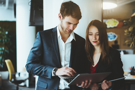 Successful young bearded man entrepreneur in the formal suit and white shirt and is having a lively debate with beautiful businesswoman in office space, showing something on the screen of the laptop Banco de Imagens