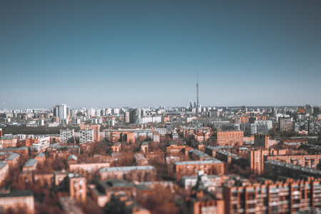 True tilt-shift urban landscape with focus point in the middle of the image: residential districts of Moscow, Russia with many blocks of flats, clear sky and Ostankino tower in defocused background