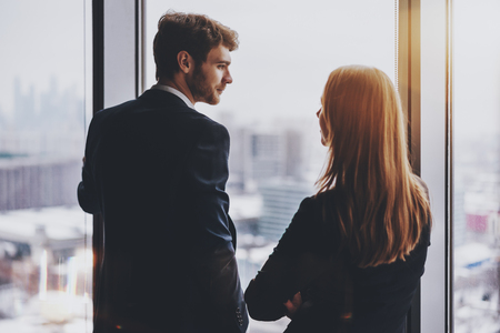 Young handsome bearded man entrepreneur in formal suit is having business conversation with his female colleague while both standing near office window Standard-Bild