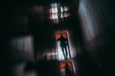 View from behind of silhouette of man entrepreneur having phone talk while moving away inside of dark office hall with multiple glass and mirror reflections, and strong chromatic aberrations