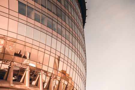 Fragment of a glassy facade of a modern curved office building, side view with offices overlooked behind windows, with clear sky on the right; exterior of a business skyscraper with reflections