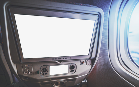 Empty white mockups of aircraft multimedia screens with remote control, close-up view of blank template of airplane monitor in passenger seat: many buttons and sockets, wide-angle shot