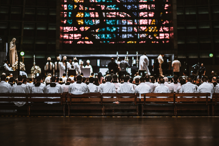 Rear view of the crowd of novices in white shirts sitting on the long wooden benches in a dark Catholic cathedral interior during a Christmas
