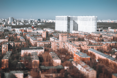 True tilt-shift cityscape: multiple five-story blocks of flats houses, modular prefabricated buildings of the Khrushchev era in Moscow, Russia; big multi-storey residential building in the background Banco de Imagens