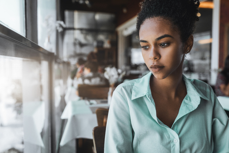 Portrait of a young beautiful Brazilian girl sitting in the cafe and wistfully looking aside; a charming African American female in a teal striped shirt is waiting for her friend in the restaurant