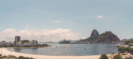 Panoramic view of Rio de Janeiro from a high point: Botafogo district with bay, multiple yachts in the water, Sugarloaf mountain with its cableway, hotels and residential houses in the distance