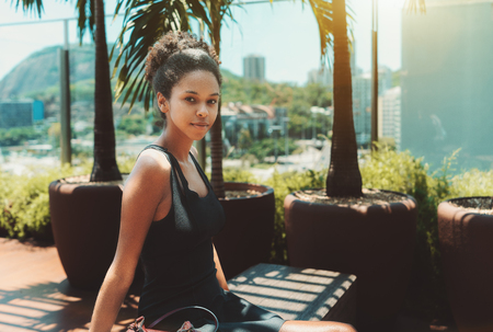 Young cutesmiling Afro American girl in a black dress is sitting on a wooden bench of the top-floor opened terrace with palm tree near her and cityscape in a defocused background
