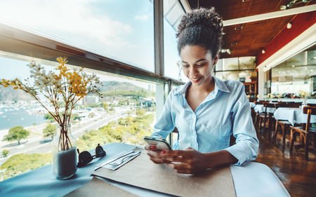 Young smiling lovely Brazilian girl is waiting for her food order while sitting next to the window in a luxury restaurant on the roof of a house and having online chat in smartphone with her friend