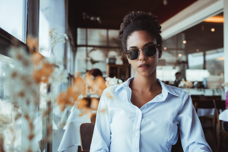 Elegant classy Brazilian girl in sunglasses is sitting inside of a luxury restaurant; young black female in a bright shirt and dark glasses is waiting for her food order in a luxurious cafe Banco de Imagens
