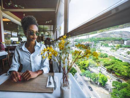 Elegant serious Brazilian girl in sunglasses is waiting for her food order while sitting in the restaurant on a high floor next to the window with a beautiful view outside; young black girl in a cafe