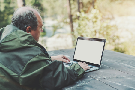 Rear view of senior man, partly bald, in a dark-green overall, sitting at the table outdoors with the laptop with white blank screen mock-up for your text message, or another content Banco de Imagens