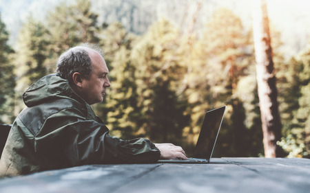 Side view of an adult male forester with a bald patch and grey hair, in the coverall, working on his laptop while sitting at a wooden table outdoors with forest in a defocused background