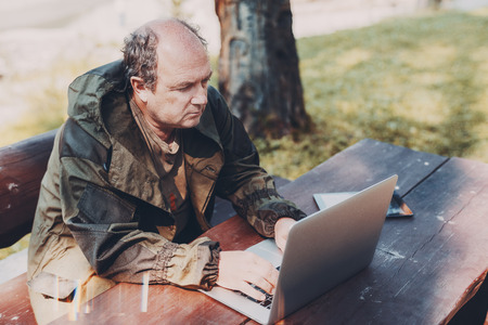 Aged partly bald man is sitting in a park with the laptop and digital tablet; adult male gamekeeper is sitting at the wooden table outdoors next to the tree and working on his netbook on a sunny day Banco de Imagens