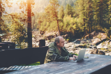 Elderly man employer is spending his vacations with work outdoors: sitting with the laptop at the wooden table with a digital tablet next to him and summer pine forest in a defocused background Standard-Bild