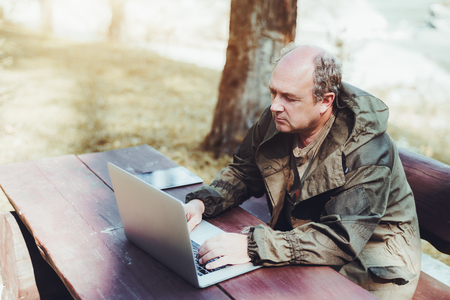 Adult male gamekeeper is sitting outdoor at a wooden table with his gadgets and using the netbook; the senior hunter in tarpaulin coverall is working on the laptop while sitting outdoors on the bench Standard-Bild