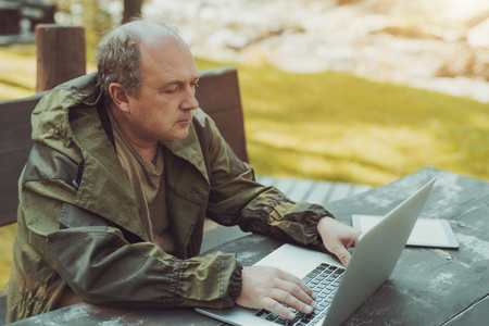 An aged serious male forester in a dark-green overalls with the bald spot and a grey hair is sittingat the table on a wooden bench outdoor and using his laptop with a digital tablet next to him Banco de Imagens