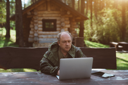 An adult serious partly bald man entrepreneur is working on the laptop during his vacations while sitting outdoors in a forest, with small shack behind and the forest in a defocused background