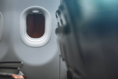 Airplane porthole during a night flight with the darkness outside, shallow depth of field and empty rows of seats; copy space on the right in a defocused area for your advertising or text message