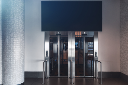 Clean and neat double elevator in a modern airport terminal or a railway depot station with empty blue banner mock-up above; paired lift in a shopping mall with the template of the banner over it