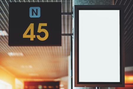 Close-up view of empty white vertical LCD screen mock-up in departure area of ??airport terminal; blank electronic informational billboard template on the column near the gate number 45 and letter