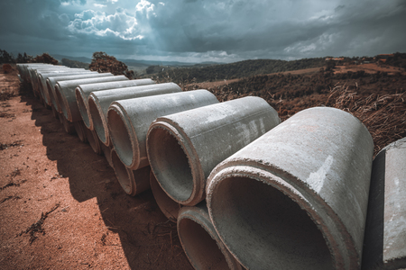 Wide-angle shot with the two rows of concrete or cement constructional pipes laying one on one, which used for the creation of sewerage systems and drain shafts; hills behind and sun rays