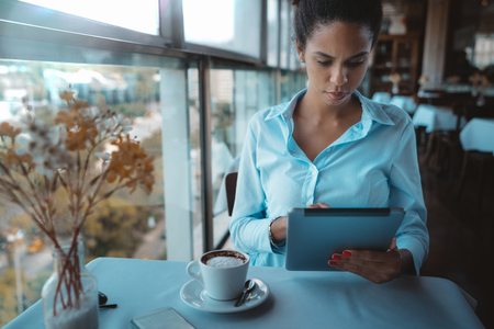 A pensive young woman entrepreneur in a teal shirt is sitting at the table in a luxury restaurant and using her tablet Stockfoto