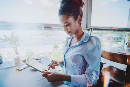 Side view of a young exquisite black girl sitting next to the window in a cafe on a high floor during a coffee break and working on her tablet pc, with the cup of cocoa and smartphone on the table Standard-Bild