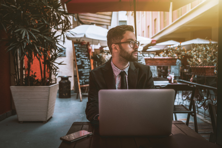 Young diffident bearded businessman in the glasses and a formal suit is sitting with the laptop in a street bar alone and thoughtfully looking aside; unconfident man entrepreneur with netbook in cafe Stock Photo
