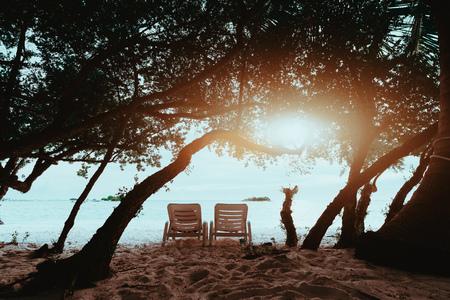 Rückansicht von zwei leeren Liegestühlen am Sandstrand, umgeben von vielen Bäumen, mit Meer und Küste vor; Liegen an der Küste mit Wasser und kleinen Inseln im Hintergrund