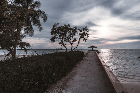 Long empty concrete pier with the sunshade at the end: palms, plants, and bushes on the left; beautiful lilac evening cloudscape, ocean and small islands in the background, Maldives Stock Photo