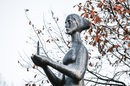 Side view of a bronze sculpture, part of a monument of the Unknown Warrior: a grieving woman holding burning candle in hands, autumn oak trees with dry leaves in the background, overcast sky