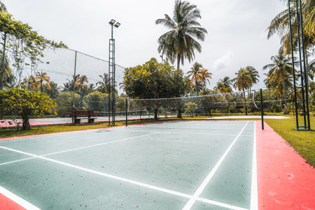 Side wide-angle view of the badminton court on a summer day: red and green field with marking on the ground, multiple palm trees and other plants around, other volleyball and tennis courts near Stock Photo