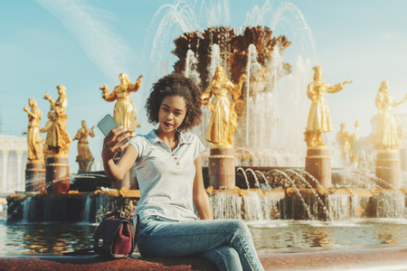Charming black girl with curly afro hair is using her smartphone for taking selfie, while sitting in front of the fountain with multiple golden statues in a defocused background; a bright summer day Standard-Bild