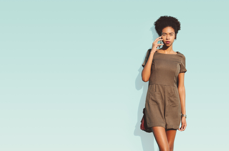 Serious cute young African-American female student is having a phone conversation, standing in front of solid isolated bluish background with copy space place for advertising, text message or logo