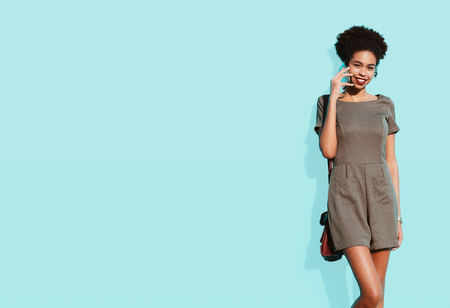 Dazzling young cheerful Brazilian female in front of a bluish wall is talking on the smartphone; smiling black girl with a curly Afro hair having a phone conversation, a solid teal wall behind her Stock Photo