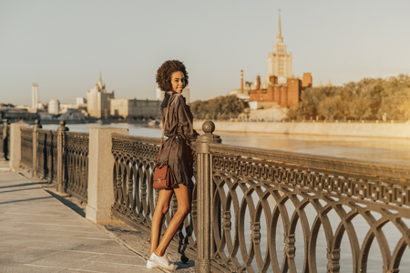 Young sexy Brazilian female tourist with curly hair is enjoying her vacation in Moscow, Russia and meeting a sunset standing near the Moscow river with the high-rise in a defocused background Stok Fotoğraf