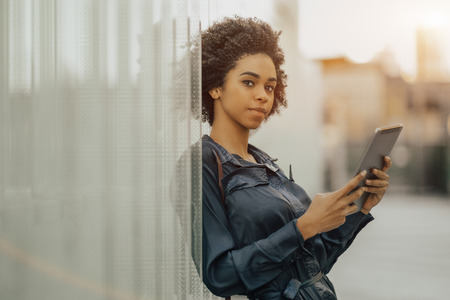 Portrait of a beautiful curly African-American girl standing next to the wall made of parallel glass blocks and holding a digital tablet; charming young black female with a tablet pc leaning at wall
