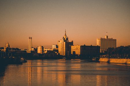 Cityscape of Moscow, Russia during the sunset: Moscow river in the foreground, silhouettes of the White House, the high-rise with the spire, two chimneys and other buildings lit by orange evening sun