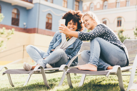 Two young beautiful laughing girls of different races are sitting outdoors on the recliners on the lawn and taking the selfie using the smartphone; interracial female couple photographing on cellphone Standard-Bild