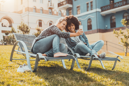 Happy cute girls of different races are sitting on the recliners on the spring meadow and taking the selfie using the smartphone; Caucasian and African-American females photographing on the cellphone