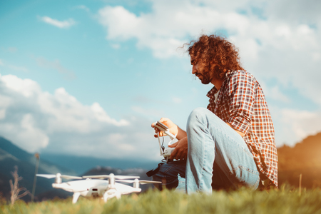 Side view of a bearded curly guy sitting alone on the mountain glade and putting a route into the remote controller of his quadcopter standing next to him in a defocused foreground; sunny summer day Stock Photo