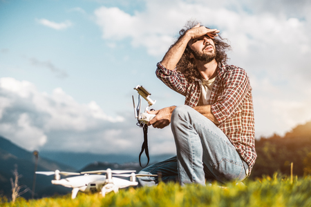 Bearded curly adult hipster man in checkered shirt is checking out the weather while sitting next to his drone on the ground and preparing to launch this quadcopter to film the mountains behind him